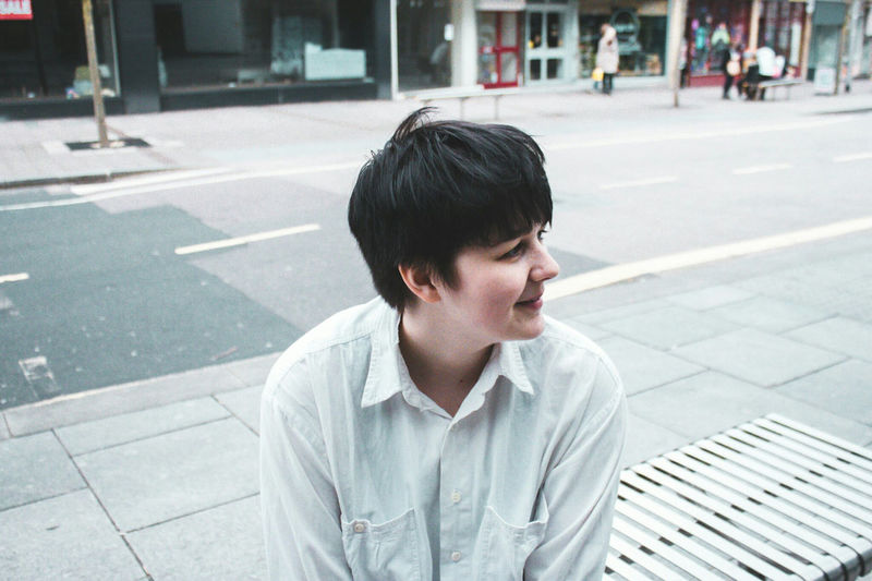 Smiling young woman sitting in city