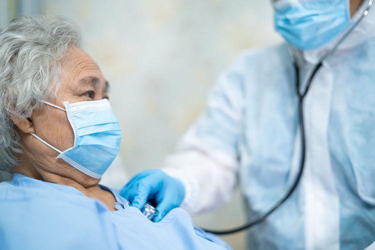 Senior woman wearing mask getting checkup