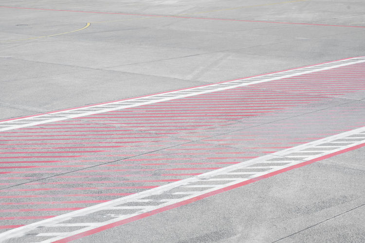 Copy Space Aerospace Industry Airport Airport Runway Asphalt Backgrounds Day Dividing Line Full Frame Gray Guidance High Angle View Marking No People Outdoors Pattern Red Road Road Marking Side By Side Sign Sport Striped Symbol Transportation