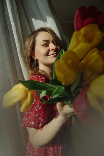 Young woman is playful natural beauty in red dress with  holding lush blooming tulips. spring mood