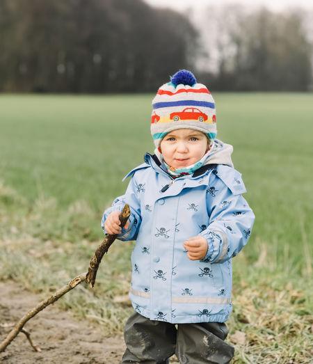 Boy in warm clothing standing on field