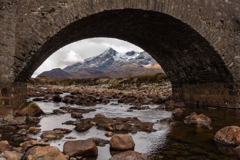 Arch bridge over river with mountains in background