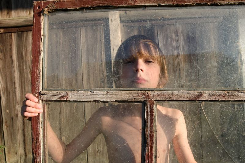 Portrait of shirtless boy looking though window