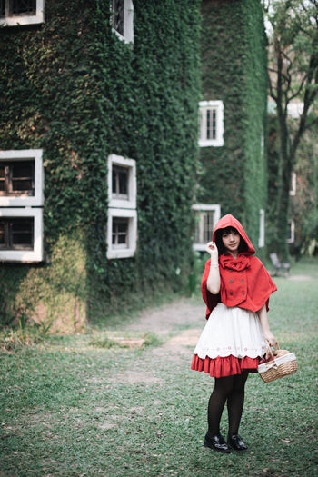 Full length of woman in little red riding hood costume holding basket while standing against building