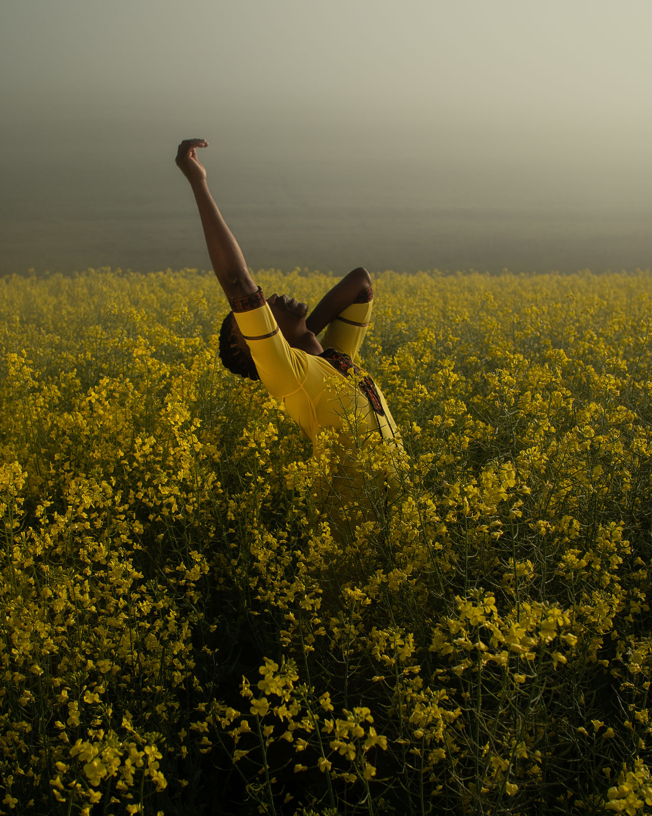 Young man standing amidst yellow flowers on oilseed rape landscape