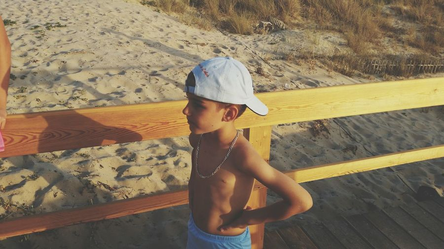 Cute shirtless boy standing on sand at beach