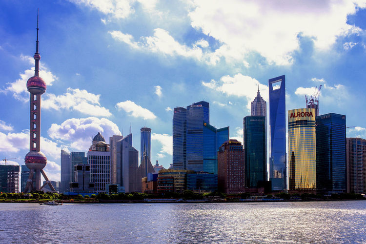Modern Buildings By Huangpu River Against Cloudy Sky