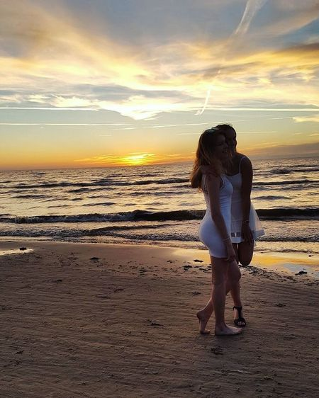 Full length of woman standing on beach against sky during sunset