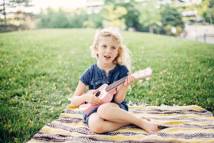 Girl sitting with musical instrument on grass