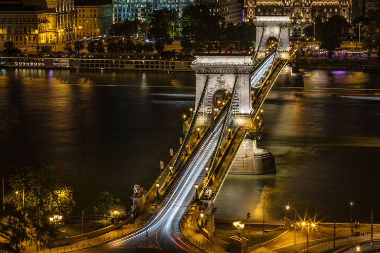 Illuminated Szechenyi Chain Bridge Over River At Night