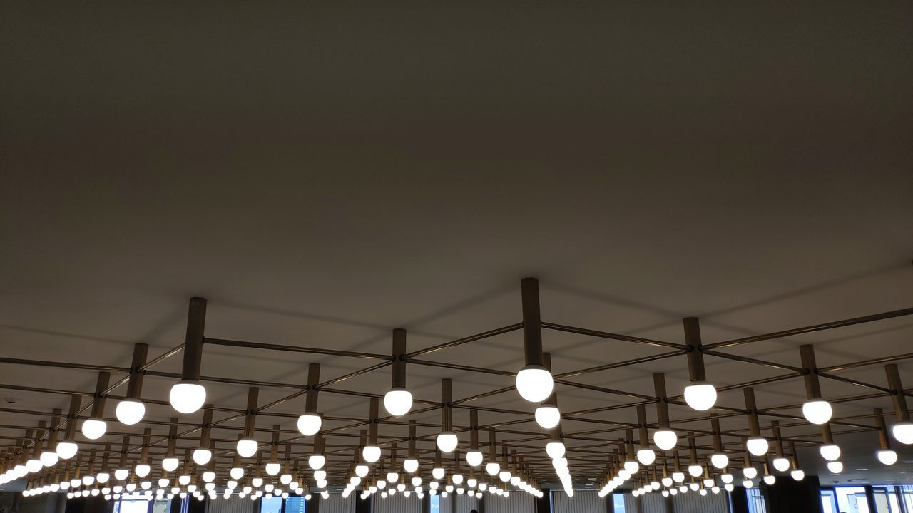 illuminated, lighting equipment, copy space, sky, low angle view, architecture, night, built structure, electricity, no people, in a row, light, nature, outdoors, decoration, connection, clear sky, electric light, light bulb, technology, ceiling, electrical equipment