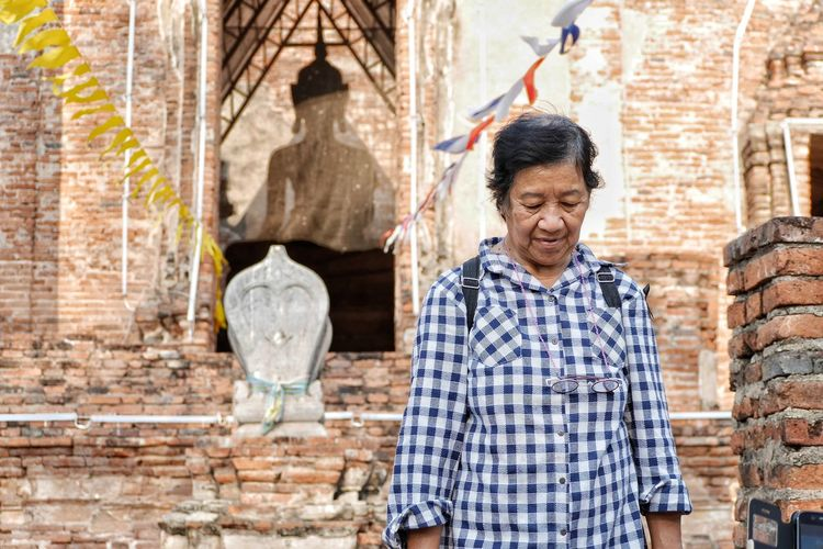 Senior woman standing against old temple