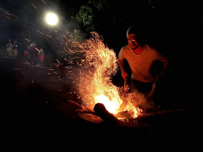 Man kneeling at campfire during night