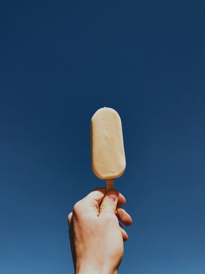 Close-up of hand holding ice cream against blue sky