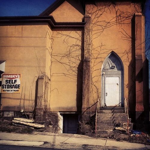 Remskys Self Storage Retired Church Deconsecrated Closed forsale hill peaked door cracked plaster creeping vines 1900s rusted handrail sideentrance brokenconcrete ruraldecay gothic creepy