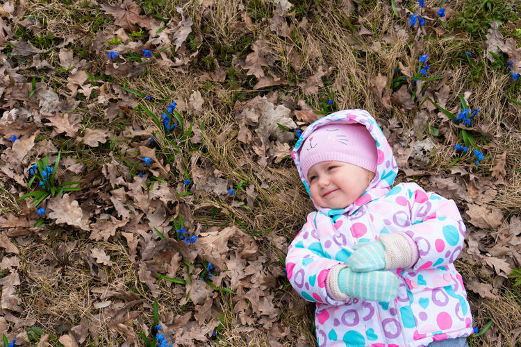 Cute baby girl lying down on autumn leaves outdoors