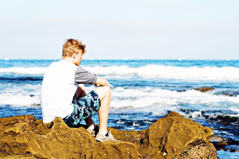 Man sitting on rock by sea against sky during sunny day