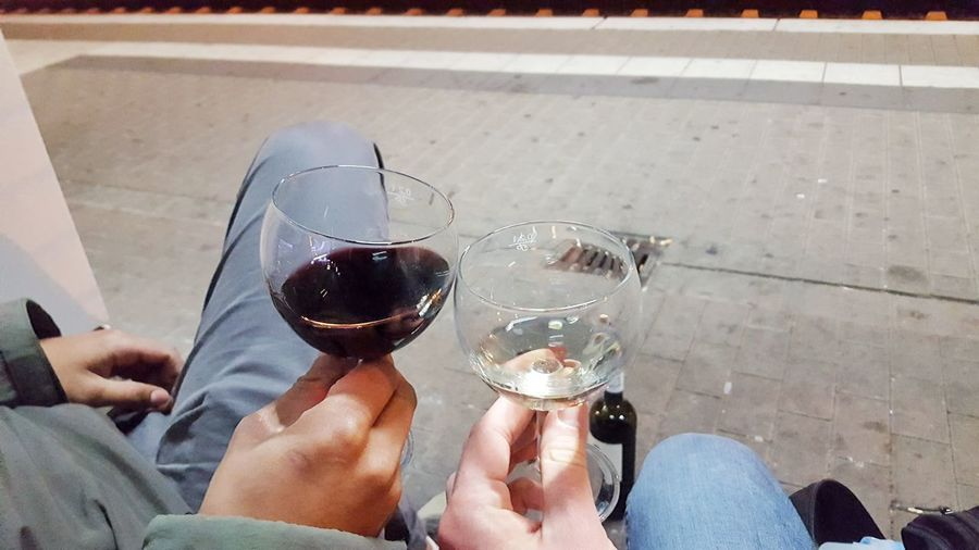 Two male hands holding wine glasses with trainstation platform in background Cheerful Trainstation Platform Wine Glasses White Wine Red Wine Black Hand Tolerance Black Skin Hand Holding Celebration Streetphotography Friendship Together Men Cheers Clink Glasses Low Section Women Men The Art Of Street Photography
