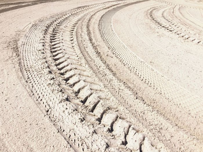 High Angle View Of Tire Tracks At Sandy Beach