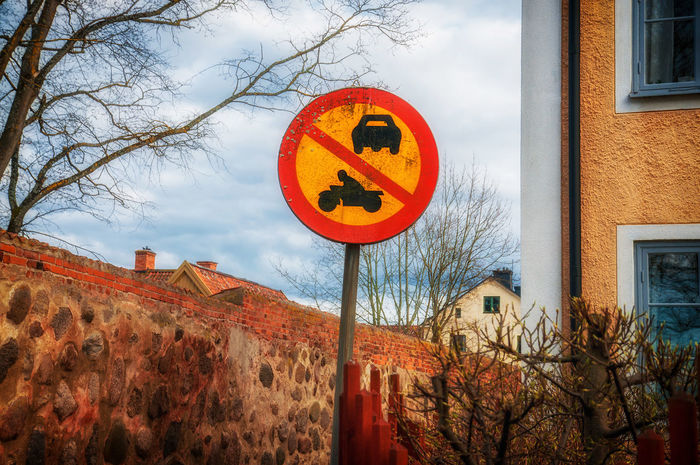 No traffic sign Alley Architecture Built Structure Cloud Cloud - Sky Cloudy Day Information Information Sign Low Angle View Medieval No People No Traffic Orange Color Outdoors Road Sign Sky Small Sweden Town Traffic Sign Tree Vadstena Wall