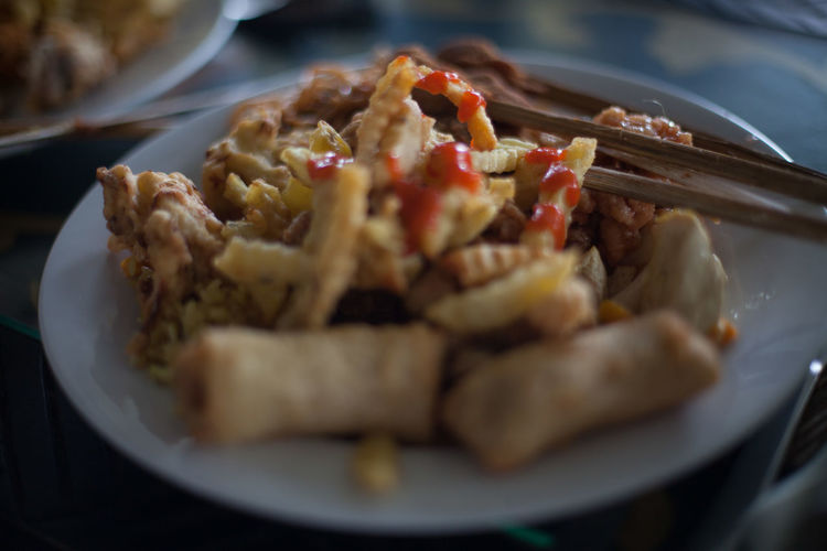 French fries and spring rolls on plate