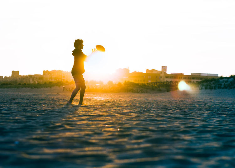 Side view of young man playing rugby at beach against clear sky during sunset