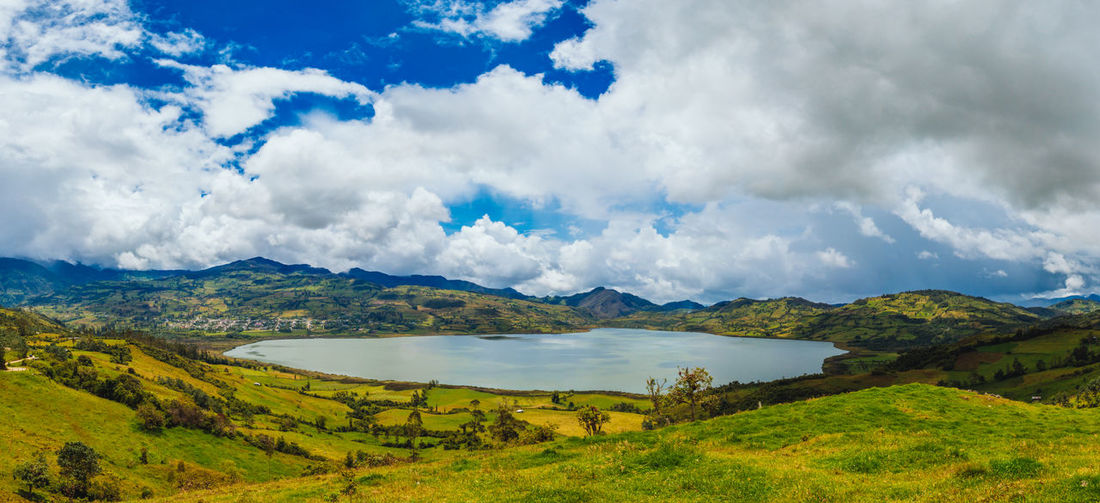 Scenic view of lake amidst hills against cloudy sky