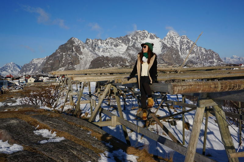 Full Length Of Woman Sitting On Wooden Structure Over Snow Covered Landscape