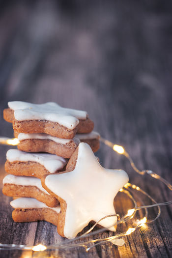 Christmas Stack Backgrounds Baked Cinnamon Cinnamon Stars Close-up Decorated Focus On Foreground Food Food And Drink Led Lights  Light String No People Star Star Shape Sweet Food Table Traditional Vertical Wooden