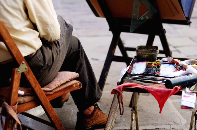 Street artist in Florence Art And Craft Paint Street Artist Chair High Angle View Human Body Part Oil Painting Photograph One Person Painting Real People Seat Street Art Street Art Photography #urbanana: The Urban Playground EyeEmNewHere