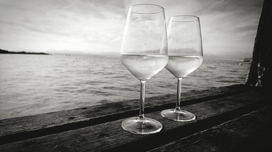 Close-up of wineglasses against lake