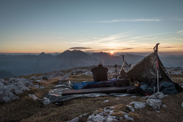 Rear view of man sitting by tent while looking at sunset over mountains against sky