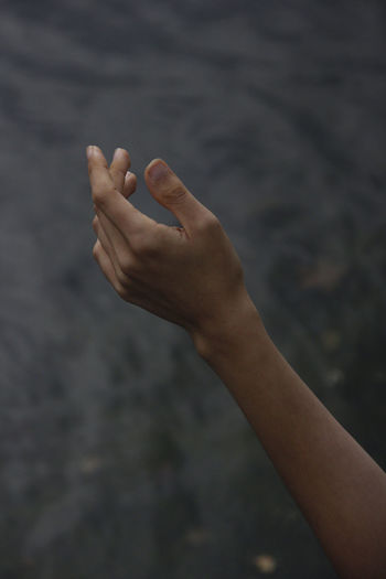 Close-up of person hand against water