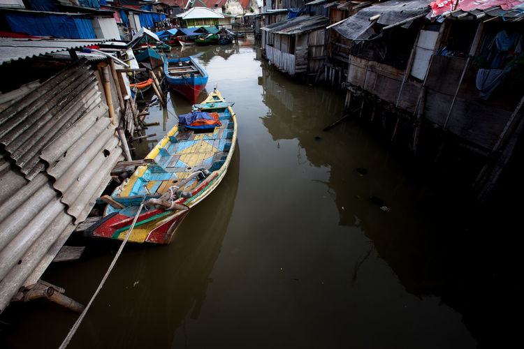 Boat moored at canal amidst houses
