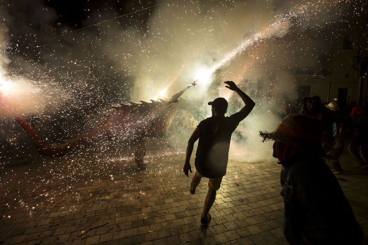 Besties a les festes de Sant Roc 2016 Besties Celebration Culture Dragon Enjoyment Fire Firerun Firework - Man Made Object Firework Display Fireworks First Eyeem Photo Light Light And Shadow Men Motion Night Outdoors Sant Roc Scene Silhouette Tranquility
