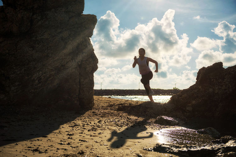 Young Asian Healthy fitness woman running on sandy beach with natural stone arch at sunrise in Rayong, Thailand. Silhouette girl photo for sport concept with nature background. Asian  Cloud Rayong Run Shades of Winter Silhouette Thailand Woman Arch Athelete Beach Female Healthy Eating Light And Shadow Ocean Sand Sea Shadow Sunrise