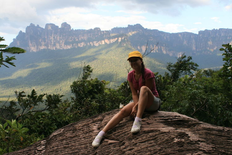 Young Woman Sitting On Rock Against Mountain At Canaima National Park