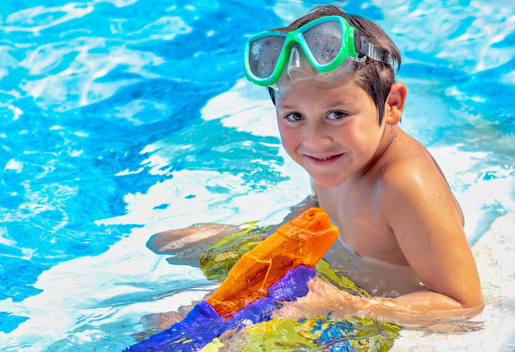 Portrait of shirtless boy swimming in pool