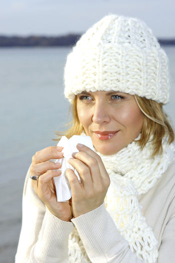 Woman with cold snuffs into a tissue Autumn Catched A Cold Tissue Walk Winter Woman Beautiful Woman Best Age Blond Hair Close-up Cold Day Lake One Person Outdoors Portrait Sick Snuffs Warm Clothing Water Winter Young Adult Young Women