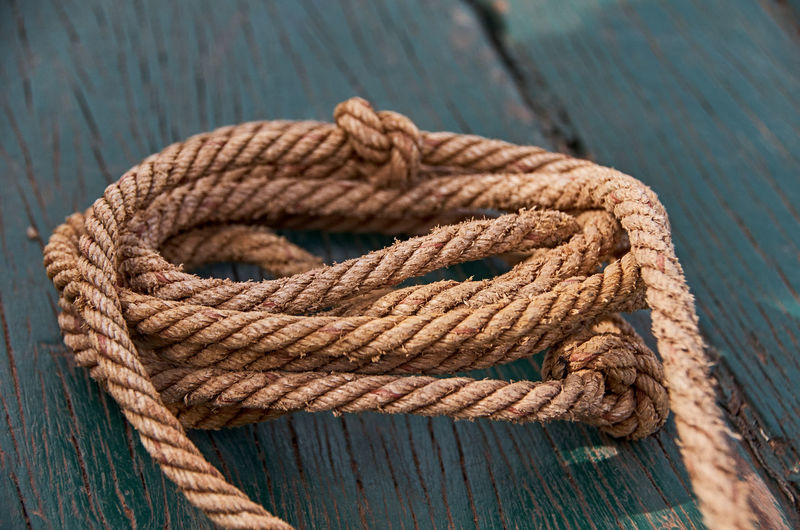 Close-up of rope on wooden plank
