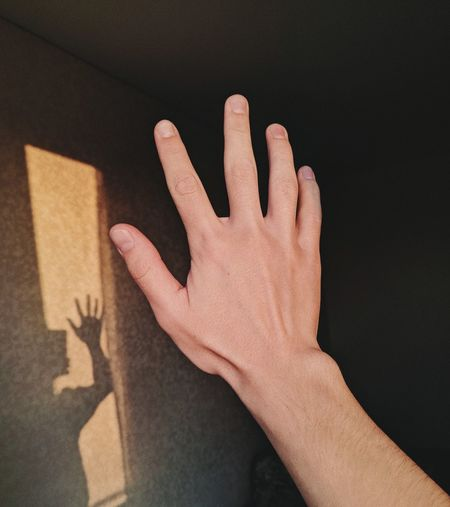 Close-up of hands against wall