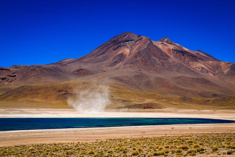 Scenic view of arid landscape with salt lake and sand storm against clear blue sky - atacama desert