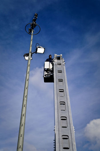 Low angle view of man on cherry picker by street light against sky