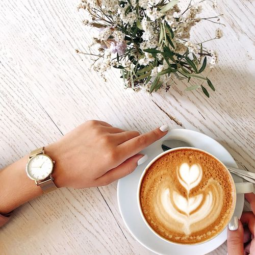 Woman holding cup of coffee Table Coffee - Drink Coffee Cup Human Hand Drink Froth Art Cappuccino Frothy Drink Human Body Part Flower Indoors  One Person Food And Drink Cafe High Angle View Wood - Material Copy Space