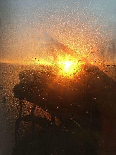 Sun seen through wet glass during sunset
