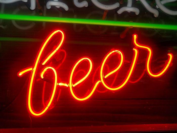 Close-up of illuminated beer text at night