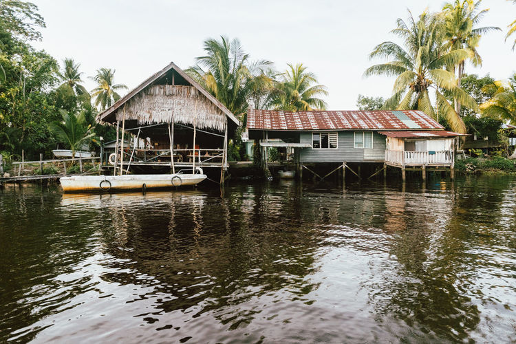 Stilt house on water by trees against sky
