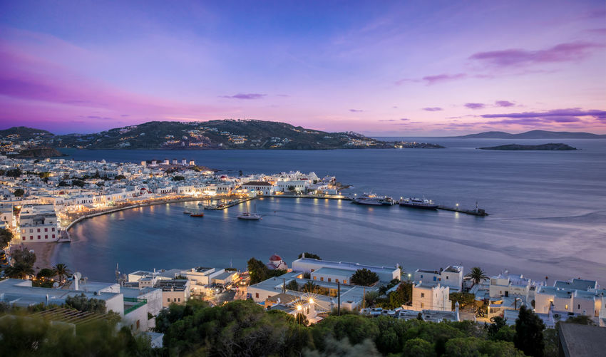 Scenic view of townscape by sea at mykonos during sunset