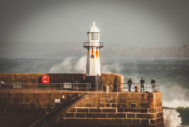 Waves splashing on lighthouse at pier against sky
