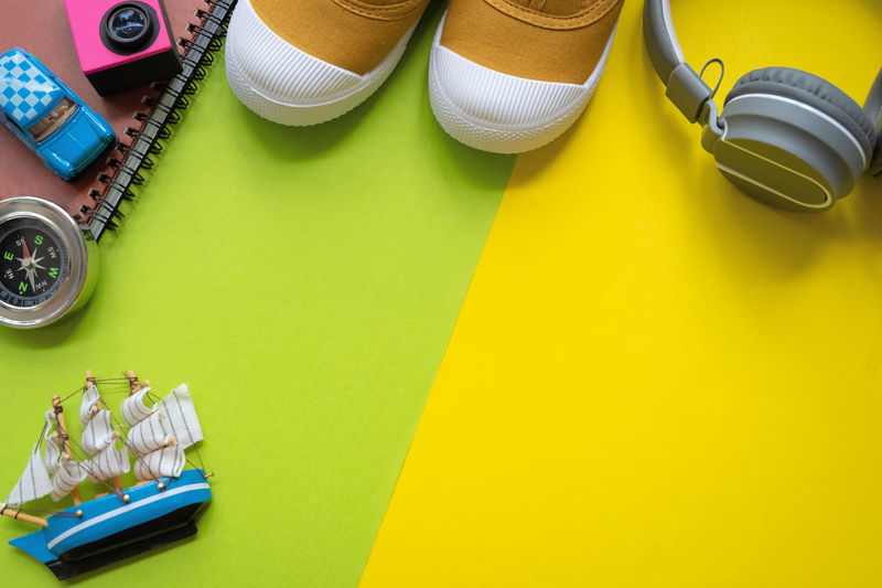 Camera Headphones Holiday Office Relaxing Traveling Vacations Book Canvas Shoes Colored Background Compass Copy Space Creativity Guide High Angle View Paper Sail Sailboat Season  Sneakers Studio Shot Summer Table Yawl Yellow